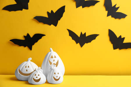Jack-o-Lantern candle holders on yellow background. Halloween decor