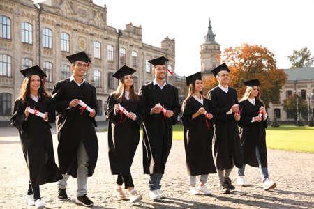 Glückliche Studenten mit Diplomen im Freien. Abschlusszeremonie Standard-Bild