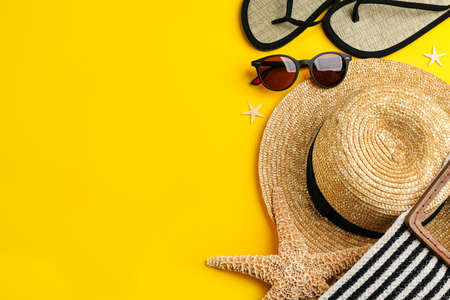 Flat lay composition with sunglasses and beach accessories on yellow background. Space for text Archivio Fotografico
