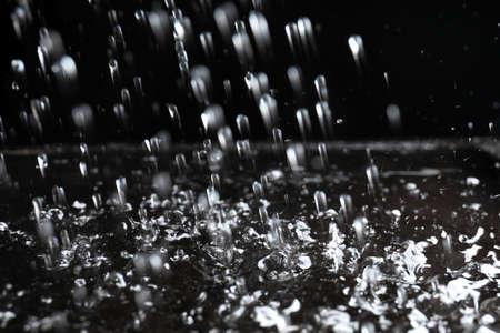 Heavy rain falling down on ground against dark background, closeup