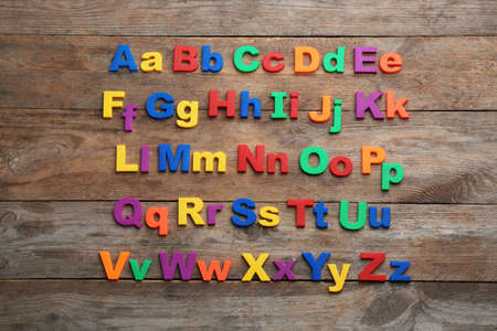 Colorful magnetic letters on wooden background, flat lay. Alphabetical order