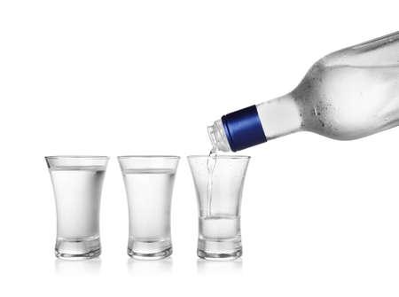 Gießen von kaltem Wodka in Schnapsglas auf weißem Hintergrund Standard-Bild