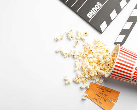 Clapperboard, popcorn and tickets on white background, top view. Cinema snack