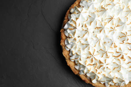Delicious lemon meringue pie on black table, top view. Space for text