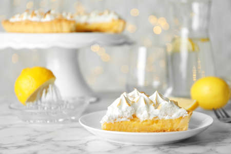 Plate with piece of delicious lemon meringue pie on white marble table Stok Fotoğraf