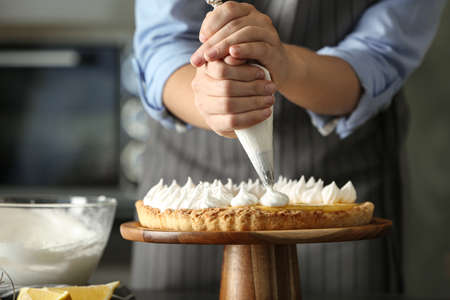 Woman preparing lemon meringue pie in kitchen, closeup Archivio Fotografico
