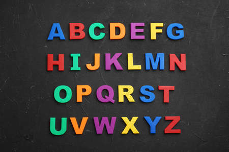 Colorful magnetic letters on black stone background, flat lay. Alphabetical order