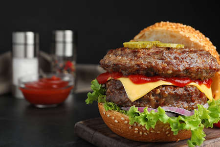 Delicious burger with meat cutlets on black table, closeup. Space for text