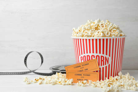 Bucket of fresh popcorn, tickets and movie reel on white wooden table, space for text. Cinema snack