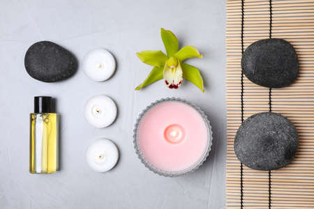 Flat lay composition with spa stones and burning candles on grey table