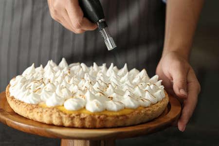 Woman toasting meringue on lemon pie with kitchen torch, closeup