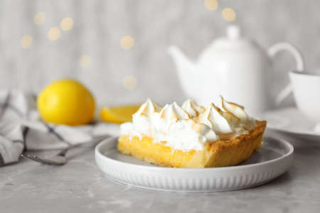 Plate with piece of delicious lemon meringue pie on light grey table 免版税图像