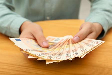 Man with Euro banknotes at table, closeup