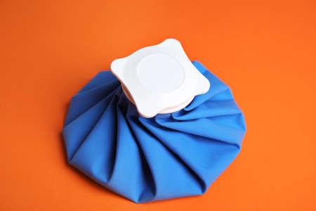 Ice pack on orange background. Cold compress