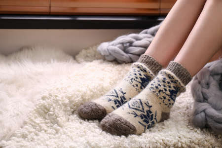 Woman wearing knitted socks on window sill indoors, closeup. Warm clothes