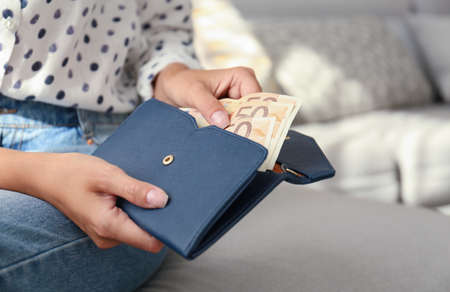 Woman putting Euro banknotes in wallet, closeup Stock Photo