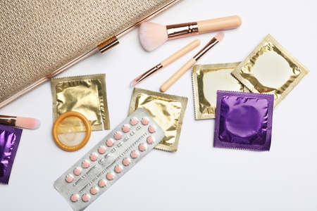 Flat lay composition with birth control pills and condoms on light background. Safe sex concept Stock Photo