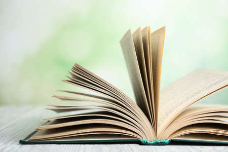 Open book on white wooden table against blurred green background, closeup