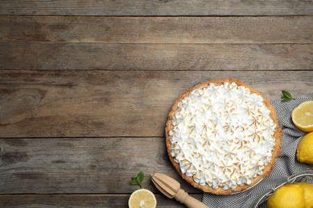 Composizione piatta con deliziosa torta di meringa al limone su un tavolo di legno, spazio per il testo
