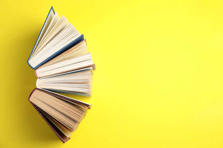 Hardcover books on yellow background, flat lay. Space for text