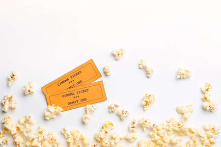 Popcorn and tickets on white background, top view. Cinema snack
