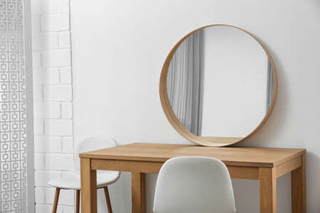 Makeup room interior with wooden table and mirror near white wall