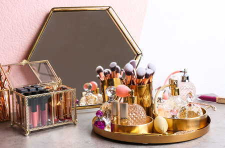 Set of luxury makeup products and perfumes on dressing table