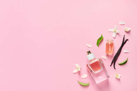 Flat lay composition with elegant perfume on pink background, space for text