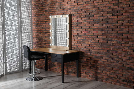 Makeup room interior with wooden table and large mirror