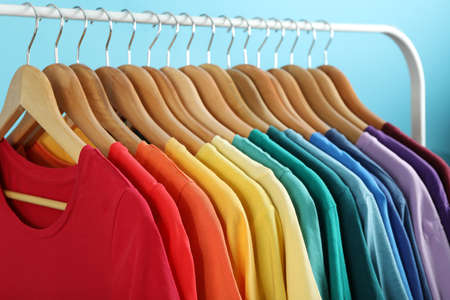 Rack with bright clothes on blue background. Rainbow colors