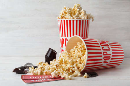 Popcorn, tickets and film footage on white wooden table. Cinema snack 版權商用圖片