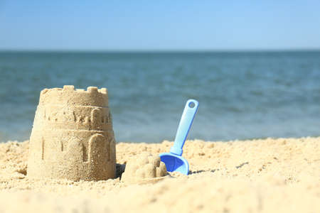 Beautiful view of beach with sand figure and shovel near sea. Space for text Reklamní fotografie
