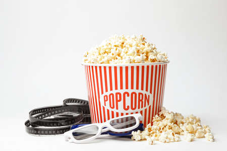 Bucket of fresh popcorn, film footage and 3D glasses on white background. Cinema snack