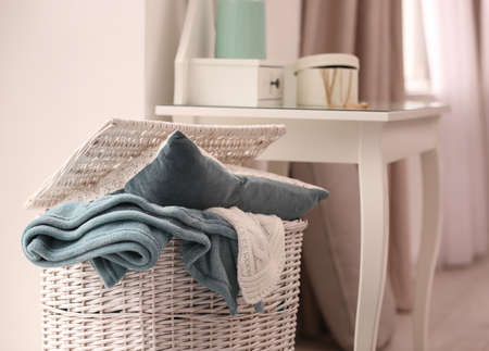 Basket with blankets and pillow near dresser indoors