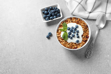 Delicious yogurt with granola and blueberries served on grey table, flat lay. Space for text