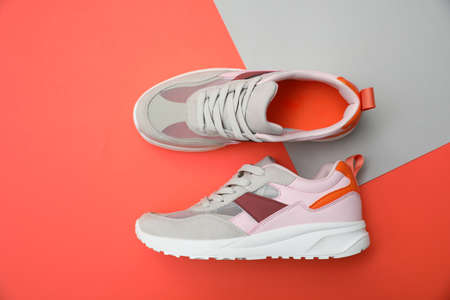 Stylish women's sneakers on color background, top view