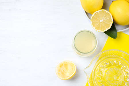 Flat lay composition with freshly squeezed lemon juice on white wooden table. Space for text