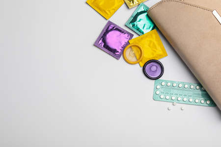 Flat lay composition with birth control pills and condoms on light background, space for text. Safe sex concept Stock Photo