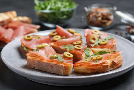 Delicious bruschettas with prosciutto and olives on table, closeup