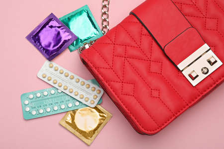 Purse with condoms and birth control pills on pink background, top view. Safe sex