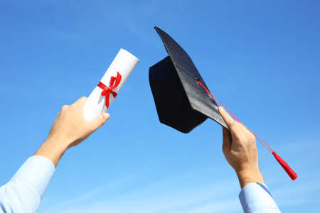 Student with graduation hat and diploma against blue sky, closeup Stockfoto