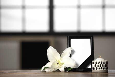 Cadre photo funéraire avec ruban noir, lys et bougie sur table en bois à l'intérieur. Espace pour la conception