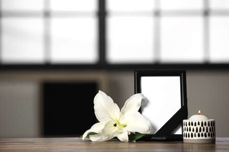 Funeral photo frame with black ribbon, lily and candle on wooden table indoors. Space for design