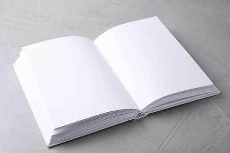 Open book with blank pages on light grey stone background. Mock up for design