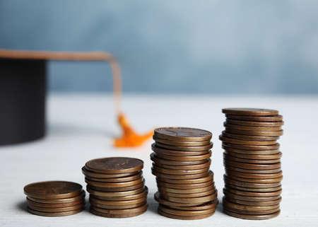 Monedas y sombrero de graduación de estudiante en mesa de madera blanca. Concepto de tasas de matrícula