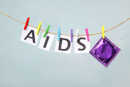 Paper sheets with word AIDS and violet condom hanging on clothesline against light grey background. Safe sex
