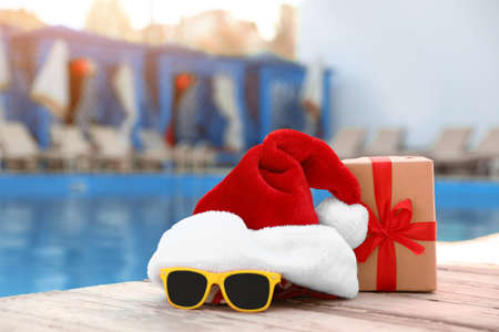 Authentic Santa Claus hat, gift box and sunglasses near pool at resort