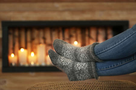 Woman wearing warm knitted socks near decorative fireplace indoors, closeup. Winter atmosphere