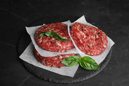 Raw meat cutlets for burger on black table Фото со стока