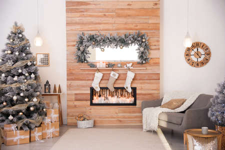 Beautiful Christmas interior of living room with decorative fireplace
